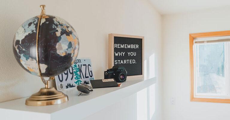 Billedet viser kontor-indretning og en lille tavle med ordene remember why you started